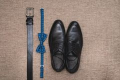Blue bow tie, leather black shoes and belt. Grooms wedding morning. Close up of modern man accessories. Look from above Stock Photography