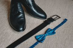 Blue bow tie, leather black shoes and belt. Grooms wedding morning. Close up of modern man accessories. Look from above Stock Image