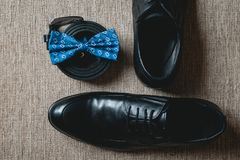 Blue bow tie, leather black shoes and belt. Grooms wedding morning. Close up of modern man accessories. Look from above Royalty Free Stock Photography