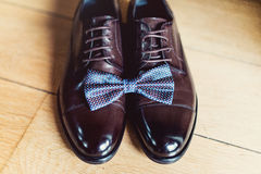 Blue bow tie on a leather brown shoes. Grooms wedding morning. Close up of modern man accessories Stock Photo