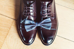 Blue bow tie on a leather brown shoes. Grooms wedding morning. Close up of modern man accessories Royalty Free Stock Photo