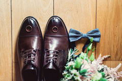 Blue bow tie, leather shoes and wedding rings. Grooms wedding morning. Close up of modern man accessories Stock Photography