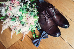 Blue bow tie, leather shoes and wedding rings. Grooms wedding morning. Close up of modern man accessories Stock Images