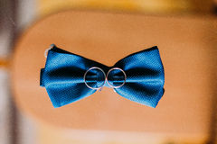 Blue bow tie and wedding rings on wooden background Stock Photo
