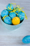 Blue and yellow easter eggs in a bowl. Blue bowl with blue decoration eggs and yellow candle egg royalty free stock photos