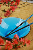 Blue bowl with chopsticks and branches Stock Image