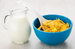 Blue bowl with corn flakes and jug of milk Royalty Free Stock Photography