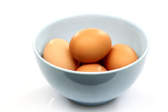 Blue bowl with eggs Stock Photos