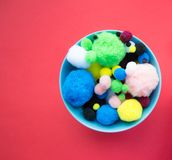 Blue bowl of fluffy ball on red background stock photo