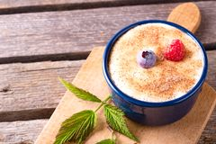 Blue bowl full of creamy dessert and with couple of berries Royalty Free Stock Images