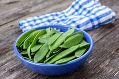 Blue bowl with green peapods Stock Photography