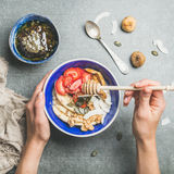 Blue bowl with healthy vegetarian breakfast in woman`s hands Royalty Free Stock Images