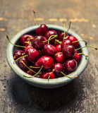 Blue bowl with sweet cherries on rustic wooden background Stock Photos