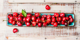 Blue bowl with sweet cherry harvest  on light wooden background Royalty Free Stock Photo