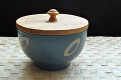Blue bowl with wooden cover. A blue bowl with wooden cover rests on grass mat Stock Images