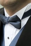 Blue Bowtie. A man wears a blue bowtie, blue vest, white shirt and black formal tuxedo Royalty Free Stock Photography
