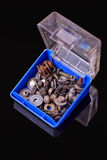Blue box with old rusty bolts, screws, brackets, various metal details on black background Royalty Free Stock Photography