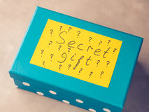 Blue box with paper card written Secret gift Royalty Free Stock Photos