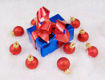 Blue box with red bow and red spheres. On the white fur Stock Photography