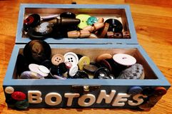 Box for clothes buttons. Blue box to store and order clothing buttons, full of buttons of all colors and sizes. The buttons sign is in Spanish language Royalty Free Stock Photo