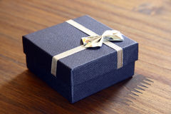 Blue Boxed Gift. Pretty little box wrapped in blue denim with small bow tied around cover.  Box is sitting on wood grained background Stock Image