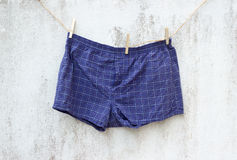 Blue boxer underwear on grunge wall. Picture stock photography