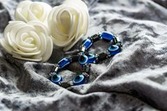Blue bracelet made of natural stones for women`s day, March 8. Figure in the form of eyes and pupil from evil eye, anger and detra. Ctors. On grey velvet with stock image