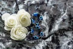 Blue bracelet made of natural stones for women`s day, March 8. Figure in the form of eyes and pupil from evil eye, anger and detra. Ctors. On grey velvet with royalty free stock photo