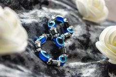 Blue bracelet made of natural stones for women`s day, March 8. Figure in the form of eyes and pupil from evil eye, anger and detra. Ctors. On grey velvet with royalty free stock photography