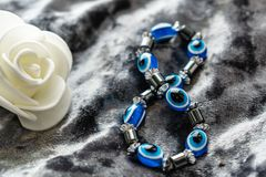 Blue bracelet made of natural stones for women`s day, March 8. Figure in the form of eyes and pupil from evil eye, anger and detra. Ctors. On grey velvet with royalty free stock photos