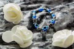 Blue bracelet made of natural stones for women`s day, March 8. Figure in the form of eyes and pupil from evil eye, anger and detra. Ctors. On grey velvet with royalty free stock image