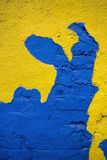 Blue brick with yellow facade. Old brick wall with cracked yellow facade and blue painting brick Stock Photography