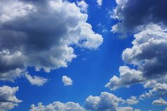 Blue bright sky with gray white clouds and sunlight Royalty Free Stock Photos