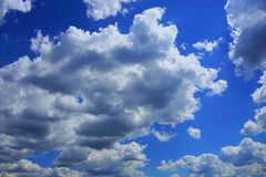 Blue bright sky with gray white clouds on a sunny afternoon Stock Images
