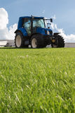 Blue Brilliant Agricultural Tractor. On Green Declivity Field Royalty Free Stock Photography