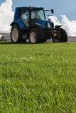 Blue Brilliant Agricultural Tractor. On Green Declivity Field Stock Photos