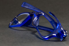 blue broken glasses on black background Royalty Free Stock Photography