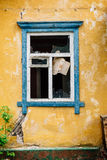 Blue broken window in old yellow abandoned house Stock Photography