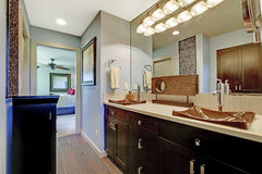 Blue and brown bathroom interior with black brown cabinets and large mirror. Stock Photography