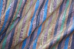 A blue brown black yellow green and pink stripes on the rough fabric with folds. rough surface texture. blue brown black yellow gr stock photos