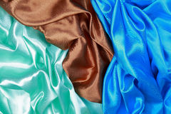 Blue and brown and light green silk satin cloth of wavy folds te Stock Photo