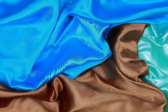 Blue and brown and light green silk satin cloth of wavy folds te Royalty Free Stock Images