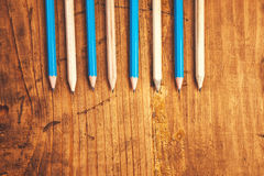 Blue and brown lined up pencils on rustic wooden table Stock Photography