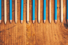 Blue and brown lined up pencils on rustic wooden table Stock Images