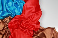 Blue and brown and red silk satin cloth of wavy folds texture ba Stock Images