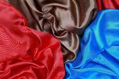 Blue and brown and red silk satin cloth of wavy folds texture ba Stock Photography