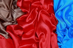 Blue and brown and red silk satin cloth of wavy folds texture ba Royalty Free Stock Photography