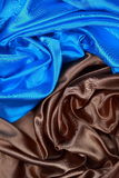 Blue and brown silk satin cloth of wavy folds texture background Royalty Free Stock Images