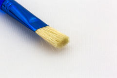 Blue brush atop textured watercolor paper Stock Image