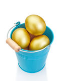 Blue bucket filled with golden Easter eggs. Stock Photos